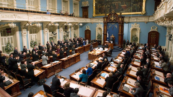 Members of the Liberal government, left, applaud after winning a non-confidence vote presented by the Opposition, right, at the legislature in Quebec City on Wednesday, Nov. 24, 2010. (Mathieu Belanger / THE CANADIAN PRESS)
