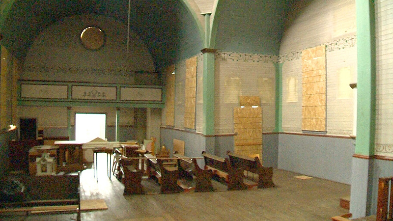 Inside the church, a number of pieces of furniture such as pews and tables appear to have been left behind.