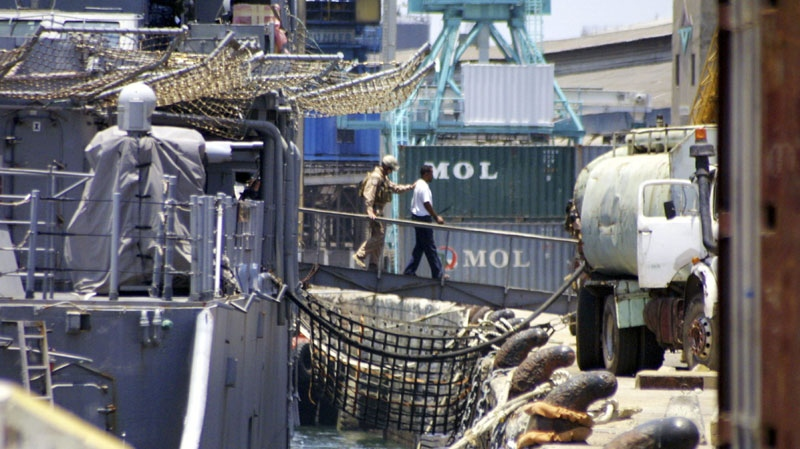 An American naval officer escorts one of the nine suspected Somali pirates as they are disembarked from the US Naval warship MV USS Princeton at the port of Mombasa, Kenya Tuesday, Oct. 12, 2010 to be handed over to the Kenyan authorities soon after the ship docked in Mombasa. (AP Photo)