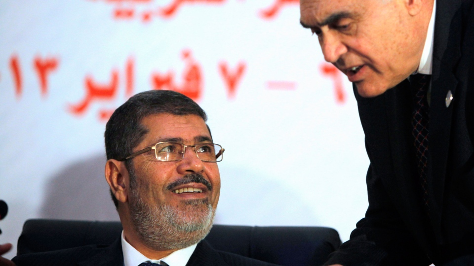 Egyptian President Mohammed Morsi smiles as he listens to his Foreign Minister Mohammed Kamel Amr during the opening of the 12th summit of the Organization of Islamic Cooperation in Cairo, Egypt, Wednesday, Feb. 6, 2013. (AP / Amr Nabil)