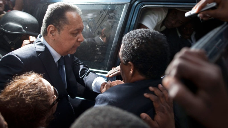 Haiti's former dictator Jean-Claude Duvalier, left, leaves court surrounded by journalists in Port-au-Prince, Haiti, Tuesday Jan. 18, 2011.  (AP / Ramon Espinosa)