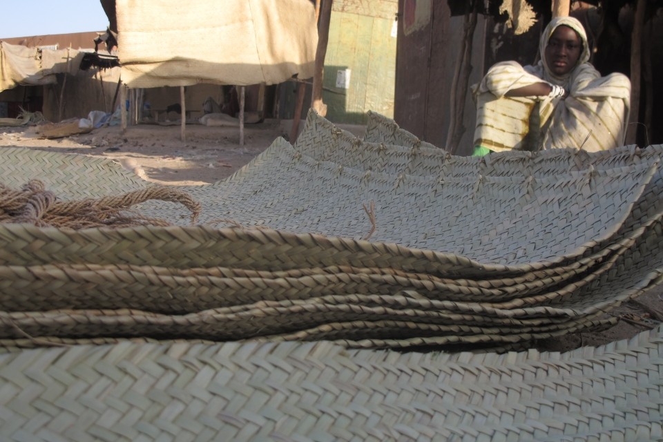 A young vendor waits for clients alongside woven reed mats of the type purchased by fleeing Islamists, apparently to camouflage their vehicles, in Timbuktu, Mali. (AP / Rukmini Callimachi)