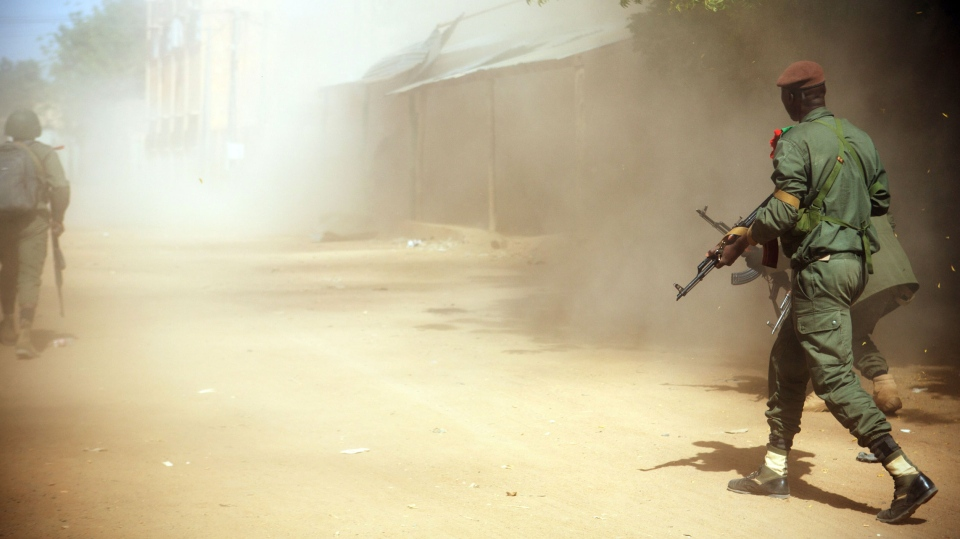 Malian soldiers walk through clouds of dust as they work with French forces to battle radical Islamic rebels, in Gao, Mali, Thursday, Feb. 21, 2013. (AP)
