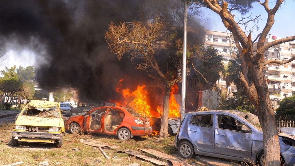 This photo released by the Syrian official news agency SANA, shows flames and smoke rising from burned cars after a huge explosion that shook central Damascus, Syria, Thursday, Feb. 21, 2013. (AP / SANA)