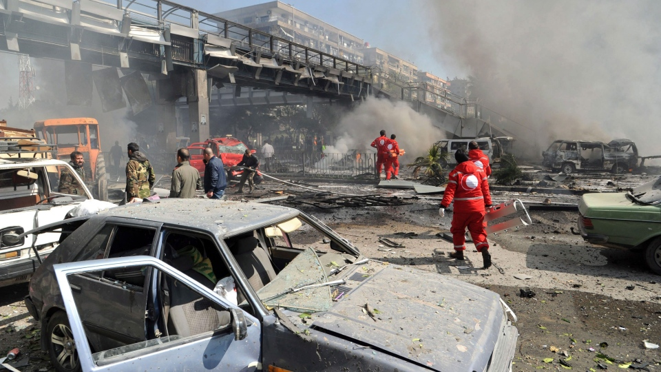 This photo released by the Syrian official news agency SANA, shows first responders working after a huge explosion that shook central Damascus, Syria, Thursday, Feb. 21, 2013. (AP / SANA)