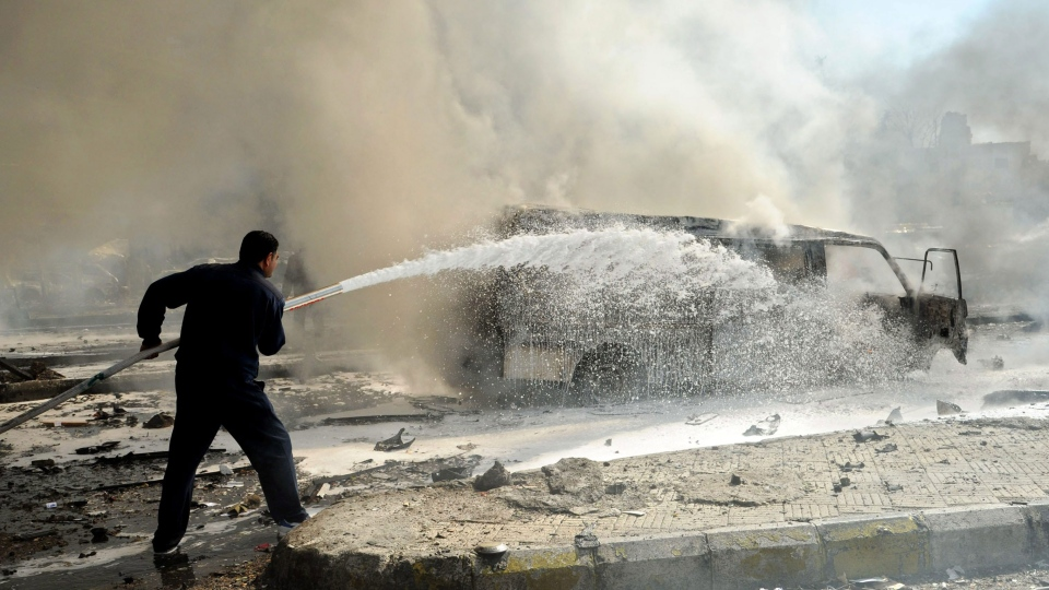 This photo released by the Syrian official news agency SANA, shows a Syrian fire fighter extinguishing burning cars after a huge explosion that shook central Damascus, Syria, Thursday, Feb. 21, 2013.  (AP / SANA)