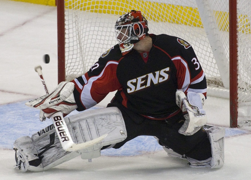 The puck rings off of the goal post behind Ottawa Senators goaltender Brian Elliott during 3rd period NHL action against the Anaheim Ducks in Ottawa on Tuesday, January 18, 2011. THE CANADIAN PRESS/Pawel Dwulit