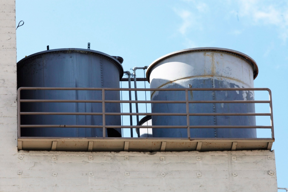 Water tanks are shown on the roof of the Cecil Hotel in Los Angeles, Thursday, Feb. 21, 2013. (AP / Damian Dovarganes)