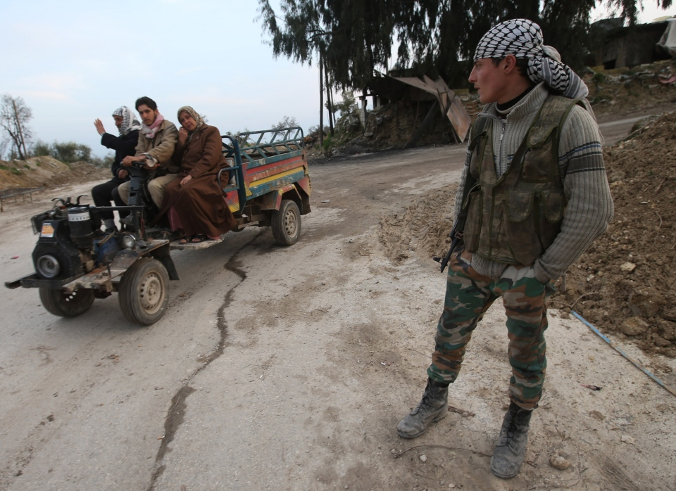 A Free Syrian Army fighter, right, watches Syrian villagers pass through a checkpoint, at the main entrance of Christian village of Yacoubieh, Syria on Feb. 21, 2013. (AP / Hussein Malla)