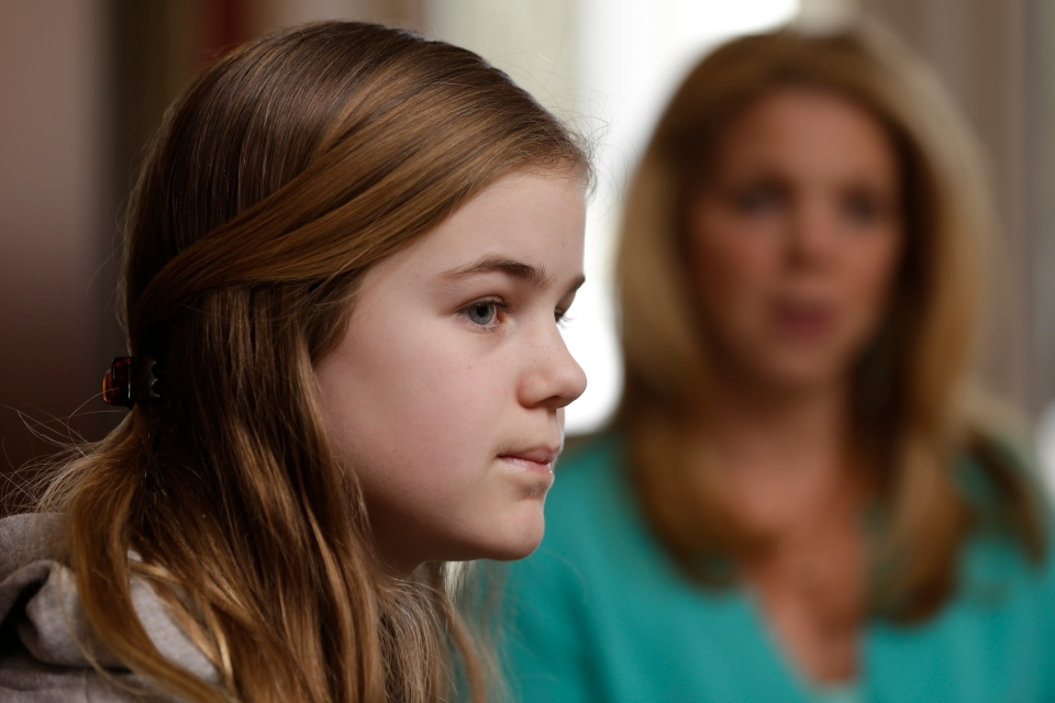Caroline Pla, 11, accompanied by her mother Marycecelia 'Seal' Pla, listens to a question during an interview Thursday, Feb. 21, 2013, in Doylestown, Pa.  (AP Photo/Matt Rourke)