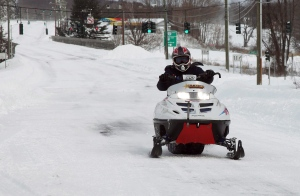 A man drives a snowmobile down a partially plowed road in Southington, Conn. on Saturday, Feb. 9, 2013. (AP / Robert Ray)