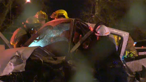 Emergency crews attempt to remove the driver of a pickup truck following an early morning crash in the city's northeast.