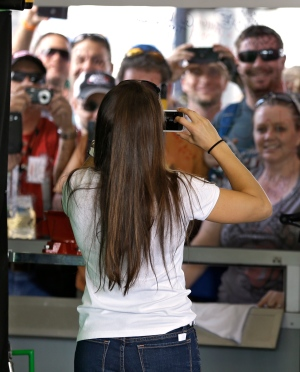 Daytona 500 pole sitter Danica Patrick takes a photo of some of her fans in the garage area during a NASCAR Sprint Cup Series auto racing practice at the Daytona International Speedway in Daytona Beach, Fla., Saturday, Feb. 23, 2013. (AP / Chris O'Meara)