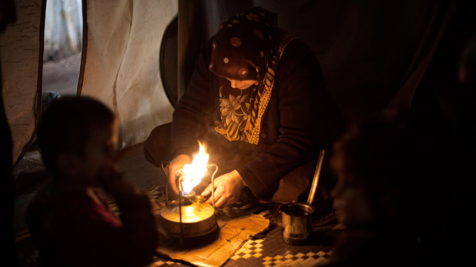 A displaced Syrian woman from Aleppo makes coffee in her tent in the Azaz camp for displaced people, north of Aleppo province, Syria, Thursday, Feb. 21, 2013. (AP / Manu Brabo)
