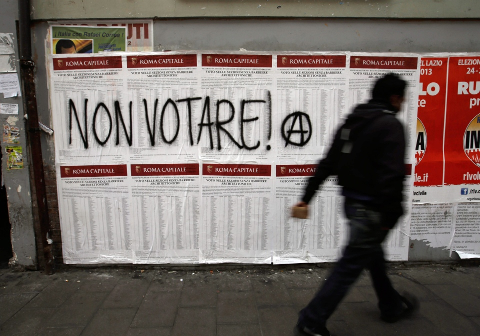 A man walks past electoral posters indicating the candidates of all parties, with an Anarchy symbol and a writing reading 'Do not vote,' in Rome, Friday, Feb. 22, 2013.  (AP / Gregorio Borgia)