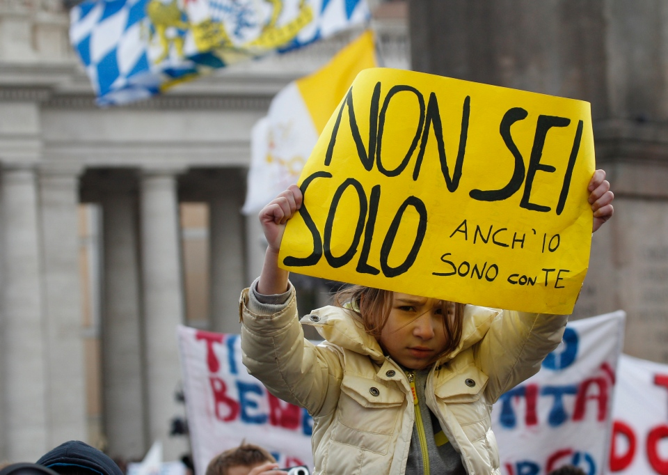 "A girl holds up a sign with a banner reading in Italian ""You are not alone, I'm also with you"" during Pope Benedict XVI's last Angelus prayer, in St. Peter's Square, at the Vatican, Sunday, Feb. 24, 2013. (AP / Alessandra Tarantino)"