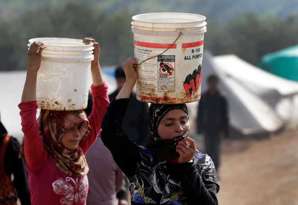 In this Tuesday, Feb. 19, 2013 photo, Syrian refugee girls carry over their heads buckets of water as they walk at Atmeh refugee camp, in the northern Syrian province of Idlib, Syria. (AP / Hussein Malla)