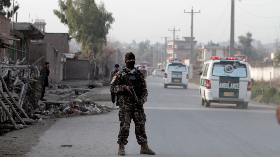 A security official stands guard the scene of a suicide car bomb attack which killed and injured several people at the National Directorate of Security in Jalalabad, Afghanistan, Sunday, Feb 24, 2013. (AP / Rahmat Gul)