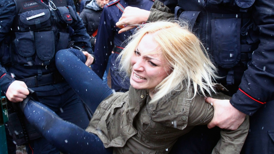 Police take away a woman protesting where former Italian Premier Silvio Berlusconi was voting, in Milan, Italy, Sunday, Feb. 24, 2013. (AP Photo / Spada, Lapresse)