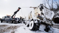 Ontario Provincial Police  officers assist drivers who were implicated in a 40-vehicle pile-up due to a white-out on highway 11 south of Orillia on Friday, Jan. 21, 2011. (Adrien Veczan / THE CANADIAN PRESS)