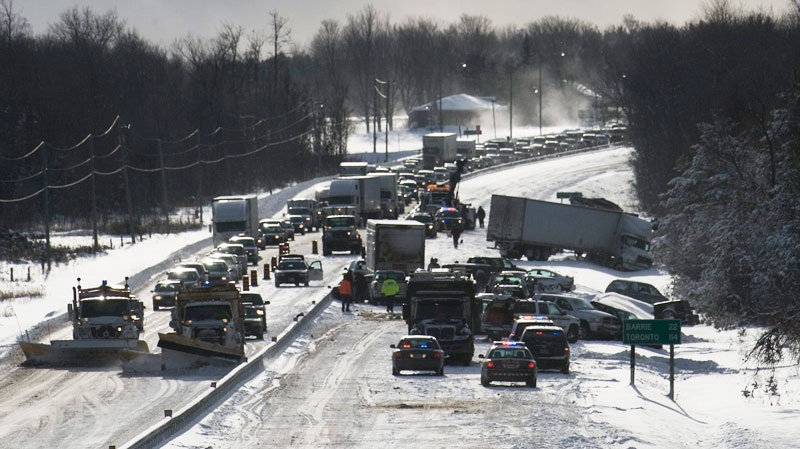 Ontario Provincial Police officers assist drivers who were implicated in a 40-vehicle pile-up due to a white-out on Highway 11 south of Orillia on Friday, Jan. 21, 2011. One woman died. (Adrien Veczan / THE CANADIAN PRESS)
