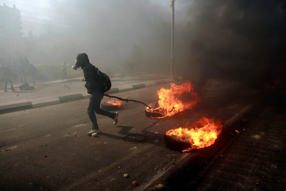 A man burns tires during a protest to support Palestinian prisoners, outside Ofer, an Israeli military prison, near the West Bank city of Ramallah, Monday, Feb. 25, 2013. (AP Photo/Majdi Mohammed)