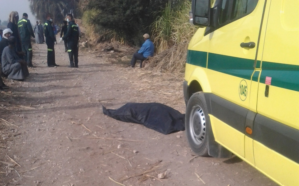 A victim of a balloon accident is seen in a body bag lying on a dirt road near the scene of a crash outside al-Dhabaa village just west of the city of Luxor, 510 kilometers south of Cairo, Egypt, Tuesday, Feb. 26, 2013. (AP / Hagag Salama)