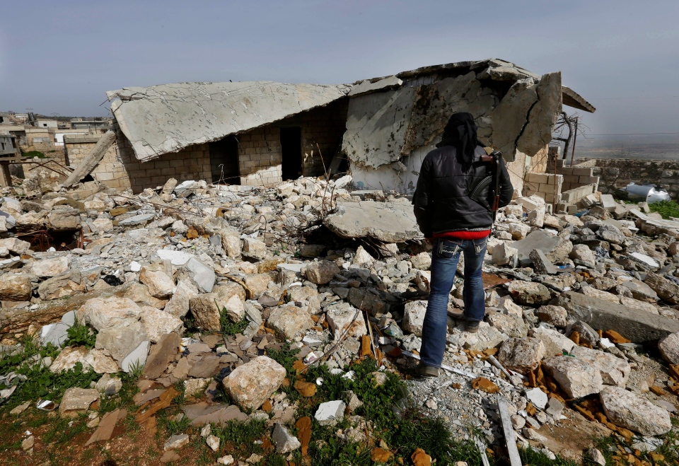 A Free Syrian Army fighter walks on rubble of a base destroyed from a Syrian forces airstrike, at Jabal al-Zaweya village of Sarjeh, in Idlib, Syria, Monday Feb. 25, 2013. (AP / Hussein Malla)