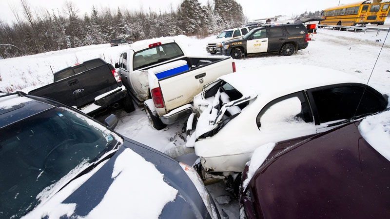 Ontario Provincial Police (OPP) officers assist drivers who were implicated in a 40-vehicle pile-up due to a white-out on highway 11 south of Orillia on Friday, January 21, 2011. (Adrien Veczan / THE CANADIAN PRESS)