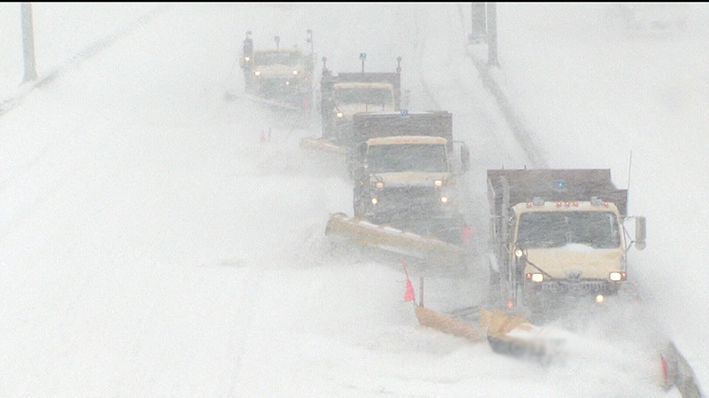 Plow trucks are on the road cleaning up after heavy snowfall in a past snowstorm in Toronto.