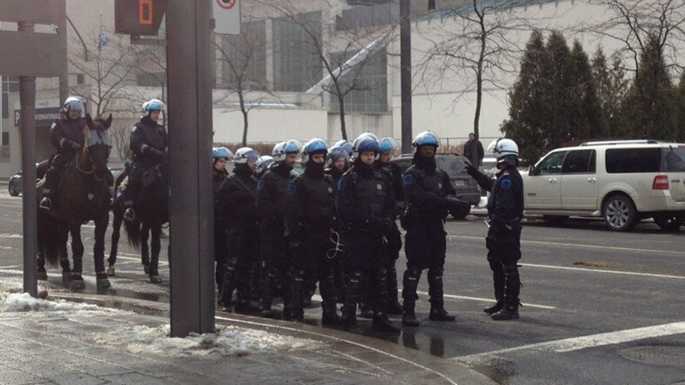Montreal police officers in riot gear stand near Victoria Square on Feb. 26, 2013 (CTV Montreal/CTV Montreal)