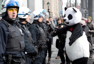 A protester known as 'Anarchapanda' walks past police during a demonstration by students in Montreal, Tuesday, Feb. 26, 2013. (Ryan Remiorz / THE CANADIAN PRESS)