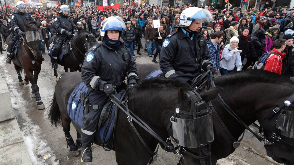 Police on horseback ride past protesting students in Montreal, Tuesday, Feb. 26, 2013. (Ryan Remiorz/THE CANADIAN PRESS)