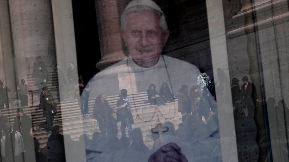 Tourists are reflected in a portrait of Pope Benedict XVI's in St. Peter's Square, a day before the Pope's last general audience, scheduled for Wednesday, at the Vatican, Tuesday, Feb. 26, 2013. (AP/Oded Balilty)