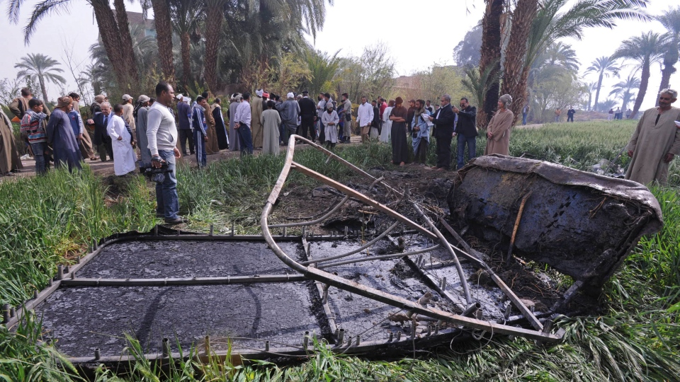 Egyptians gather at the site of a balloon crash where the remains of the burned gondola are seen, outside al-Dhabaa village, just west of the city of Luxor, 510 kilometers (320 miles) south of Cairo, Egypt, Tuesday, Feb. 26, 2013. (AP / Hagag Salama)