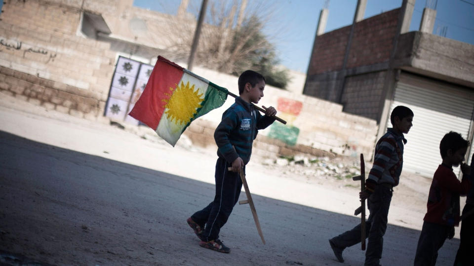 A boy holds a Kurdish flag as he and others hold toy guns on a street in Ras al-Ayn, Syria, Monday, Feb. 26, 2013. (AP / Manu Brabo)