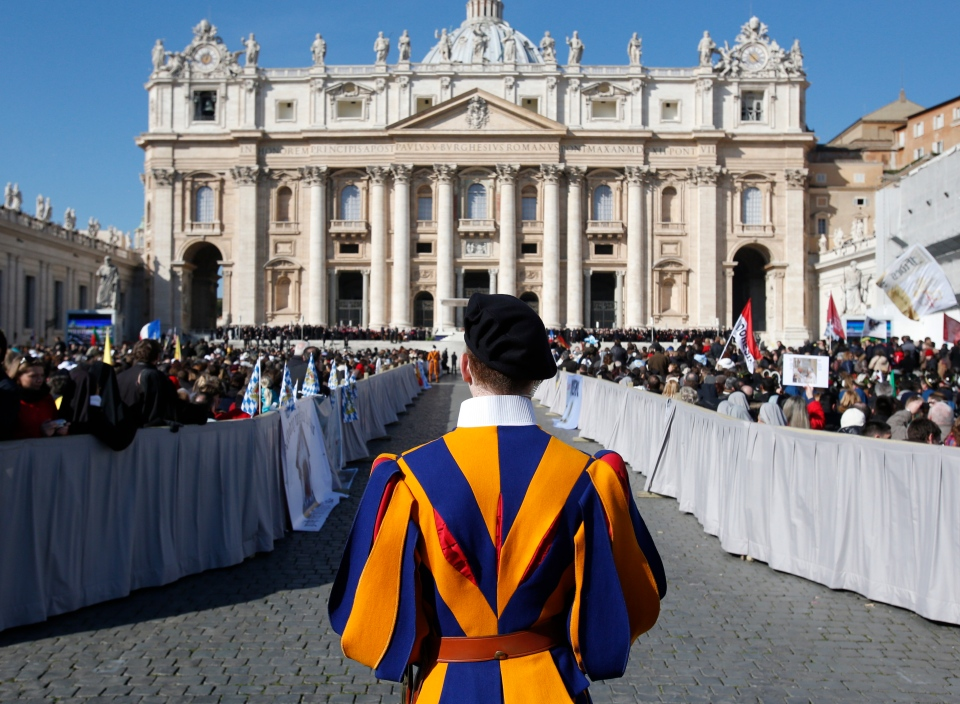 A Vatican Swiss guard stands in front of St. Peter's Basilica at the Vatican, Wednesday, Feb. 27, 2013. (AP Photo/Michael Sohn)