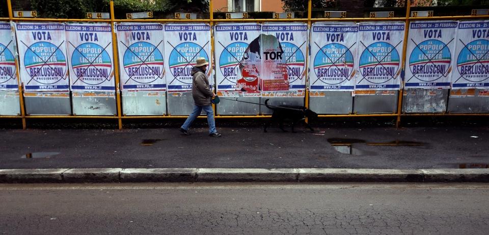 A woman walks a dog past electoral posters in Rome, Monday, Feb. 25, 2013. (AP Photo/Gregorio Borgia)