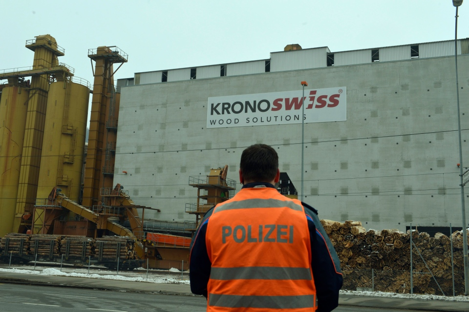 A police officer stands in front of a wood-processing company in Menznau, central Switzerland, Wednesday, Feb. 27, 2013, where several people were killed in a shooting. (AP Photo/Keystone, Urs Flueeler)