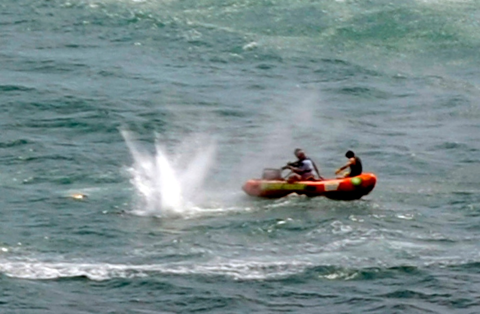 Police in inflatable rubber boats shoot at a shark off Muriwai Beach as they attempt to retrieve a body following a fatal shark attack near Auckland, New Zealand, Wednesday, Feb. 27, 2013. (AP / Ross Land)