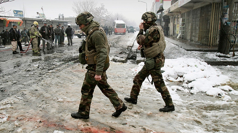 French soldiers with the NATO- led forces walk past blood stained snow at the scene of a suicide attack in Kabul, Afghanistan, Wednesday, Feb. 27, 2013.  (AP / Ahmad Jamshid)