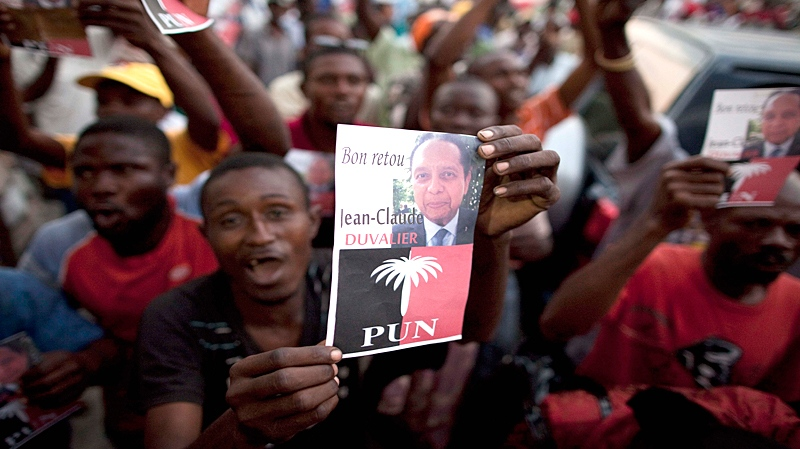 A supporter of Haiti's former dictator Jean-Claude Duvalier holds up an image of Duvalier outside the rented guest house where Duvalier is staying in Port-au-Prince, Haiti, Friday Jan. 21, 2011. (AP / Ramon Espinosa)