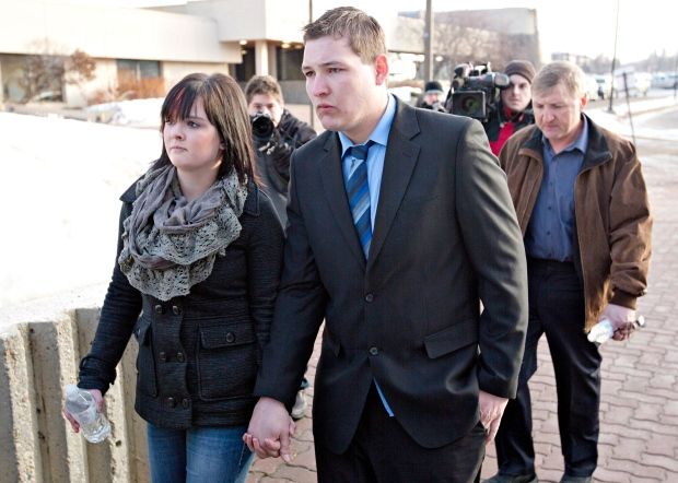 Brenden Holubowich walks with supporters as he makes his way to the courthouse for sentencing in the deaths of four high school football players, in Grande Prairie, Alta., on Feb. 26, 2013. (Jason Franson/THE CANADIAN PRESS)