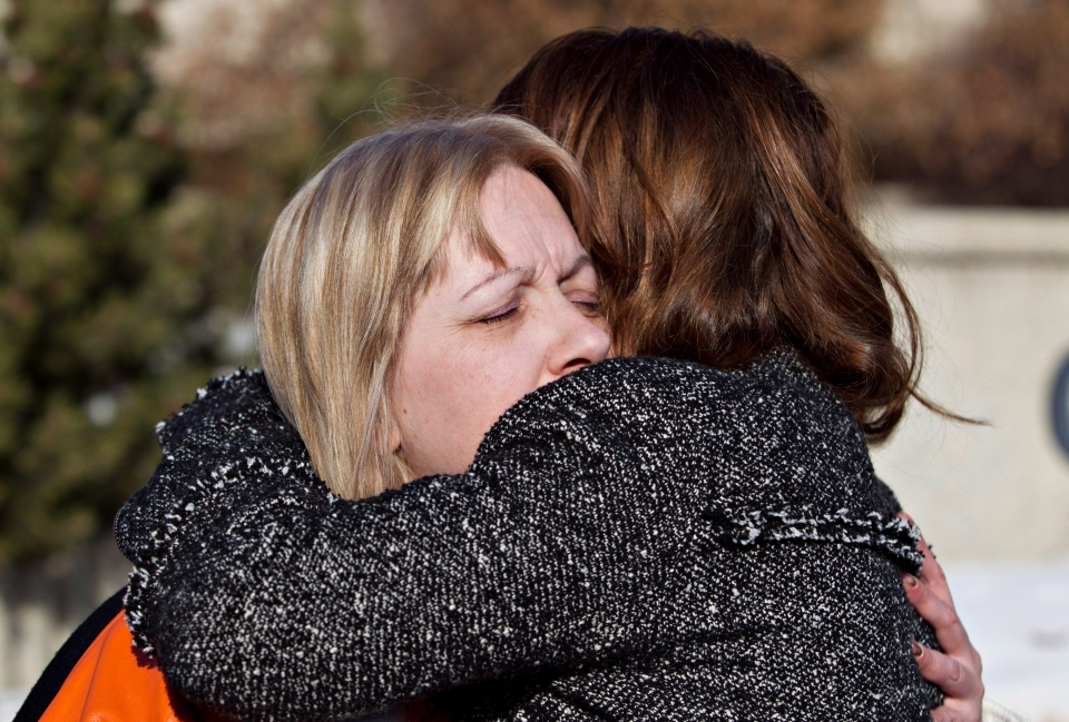 Holly Borden, mother of deceased football player Walter Borden-Wilkins, and Connie Hildebrand-Strong, mother of Tanner Hildebrand, hug outside the sentencing of Brenden Holubowich in Grande Prairie, Alta. on Feb. 26, 2013. (Jason Franson/THE CANADIAN PRESS)