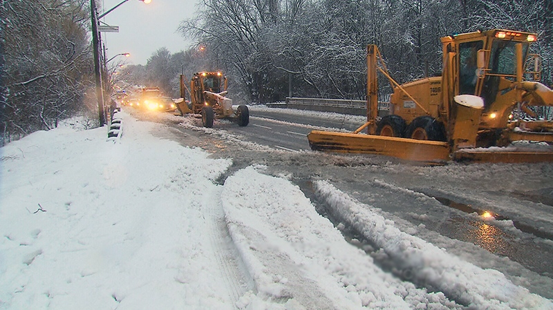 Plow trucks clean messy roads due to wet and heavy snowfall in Toronto on Wednesday, Feb. 27, 2013.