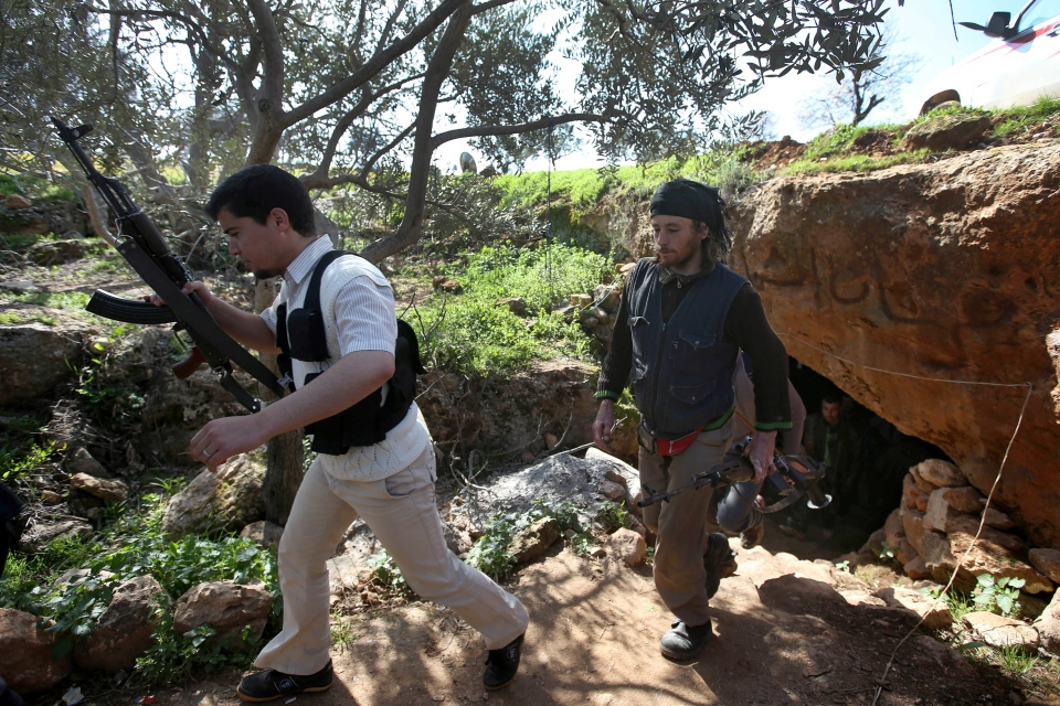 Free Syrian Army fighters from the Knights of the North brigade leave one of their caves to reconnaissance a Syrian army forces base of al-Karmid, at Jabal al-Zaweya, in Idlib province, Syria, Wednesday, Feb. 27, 2013. (AP / Hussein Malla)