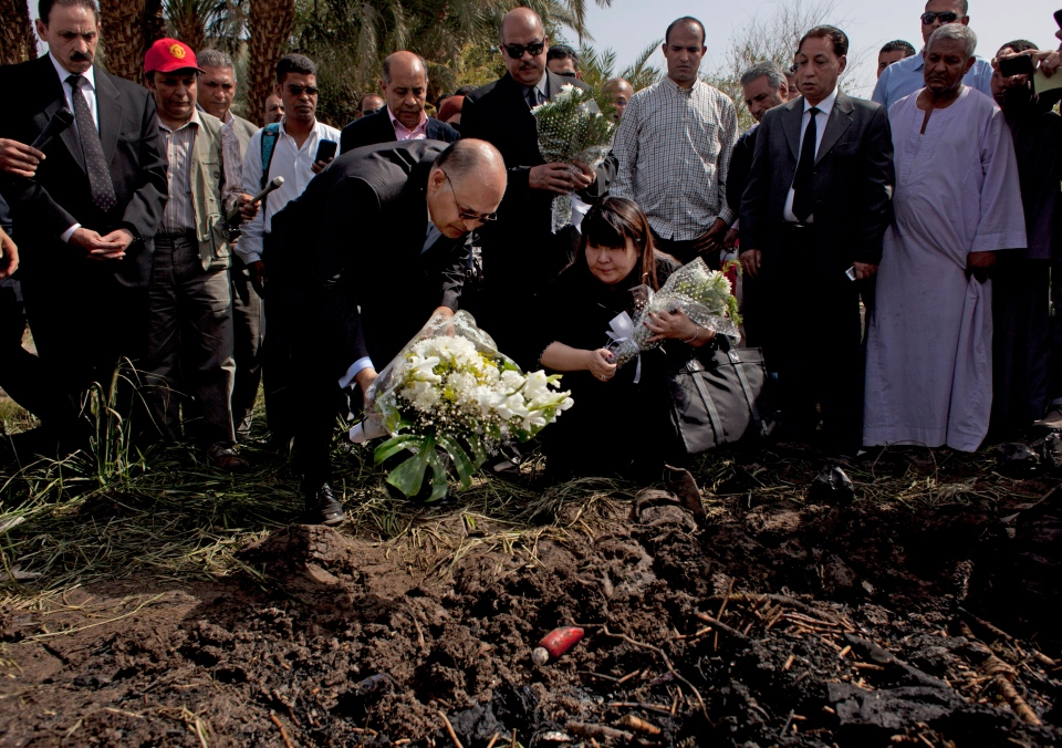 Japanese travel agent Okumura Hatsuko, bottom right, and Luxor's Govornor Ezzat Saad, bottom left, lay flowers to pay respect to Japanese tourists that died from a hot air balloon accident, in Luxor, Egypt, Wednesday, Feb. 27, 2013. (AP / Nasser Nasser)