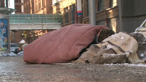 A homeless man seeks warmth under blankets on a Toronto sidewalk during a cold snap Sunday, Jan. 23, 2011.