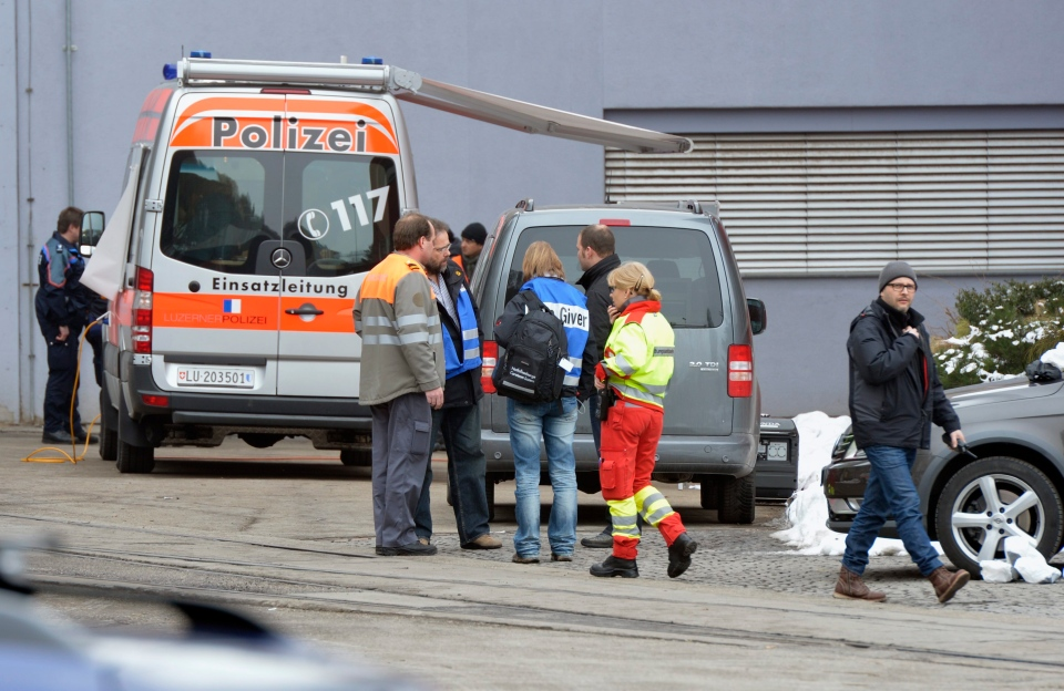 Police stand in front of a wood-processing company where several people were killed in a shooting in Menznau, central Switzerland, Wednesday, Feb. 27, 2013. (AP / Keystone, Urs Flueeler)
