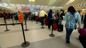 Travellers line up to check in for their flight on board a Sunwing airplane.